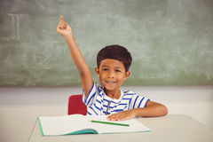 Portrait of schoolboy raising his hand in classroom Royalty Free Stock Photo
