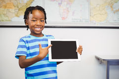 Portrait of schoolboy showing digital tablet in classroom. At school Royalty Free Stock Images
