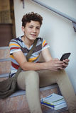 Portrait of schoolboy sitting on staircase and using mobile phone Stock Photos
