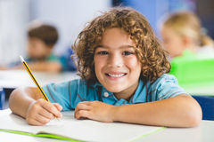 Portrait of schoolboy studying in classroom. Portrait of smiling schoolboy studying in classroom at elementary school Royalty Free Stock Photos