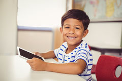 Portrait of schoolboy using digital tablet in classroom Stock Image