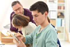 Portrait of schoolboy using smartphone in class Royalty Free Stock Images