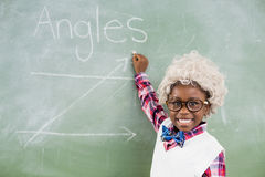 Portrait of schoolboy wearing wig doing mathematics on chalkboard in classroom Stock Photos