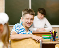 Portrait of schoolboy at workplace with teacher on background Royalty Free Stock Photos