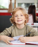 Portrait Of Schoolboy Writing In Book At Desk Royalty Free Stock Image