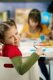 Portrait of schoolgirl in art class. Portrait of happy elemantary age child sitting at desk looking at camera in art class in primary school classroom, smiling Royalty Free Stock Photos