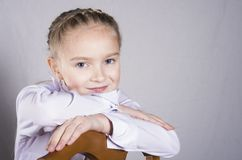 Portrait of a schoolgirl on the chair in studio Stock Photos