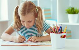 Portrait of schoolgirl at classroom writing at the table royalty free stock photography