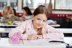 Portrait Of Schoolgirl Drawing In Book. Portrait of cute little schoolgirl drawing in book with classmates in background stock photo