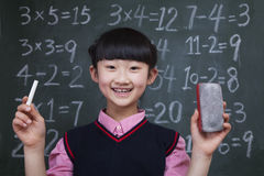 Portrait of schoolgirl in front of blackboard holding chalk and eraser Stock Images