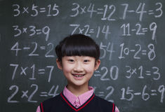 Portrait of schoolgirl in front of blackboard with math equations Stock Photo