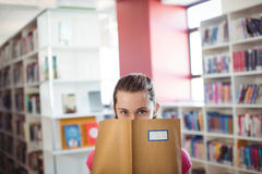 Portrait of schoolgirl hiding her face with book in library. At school Stock Image