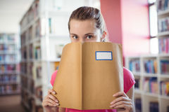Portrait of schoolgirl hiding her face with book in library Stock Image