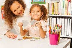 Portrait of schoolgirl holding puzzle pieces Stock Image