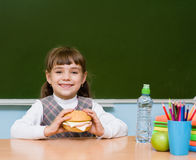 Portrait schoolgirl looking at camera while having lunch during Stock Photos