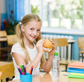 Portrait schoolgirl looking at camera while having lunch during Stock Images