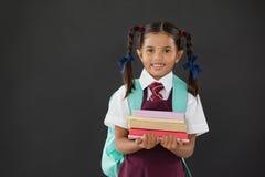 Portrait of schoolgirl in school uniform holding books against blackboard Stock Photo