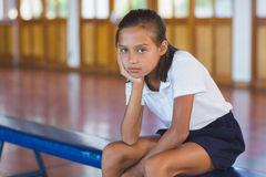 Portrait of schoolgirl sitting in basketball court. At school gym Royalty Free Stock Image