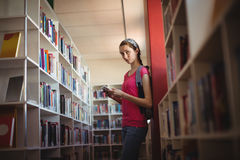 Portrait of schoolgirl using digital tablet in library Royalty Free Stock Photography
