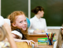 Portrait of schoolgirl at workplace with teacher on background Stock Photos
