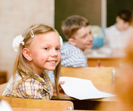 Portrait of schoolgirl at workplace with teacher on background Stock Photo