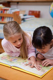 Portrait of schoolgirls reading a fairy tale. In a classroom Stock Images