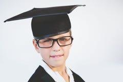 Portrait of schoolkid pretending to be graduate Stock Photos