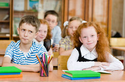 Portrait of schoolkids looking at camera at workplace Stock Photo
