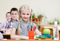 Portrait of schoolkids looking at camera at workplace Stock Photos