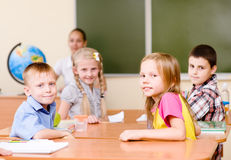 Portrait of schoolkids at workplace with teacher on background Royalty Free Stock Photography