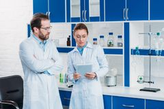 Portrait of scientific researchers in lab coats with digital tablet. In laboratory stock photos