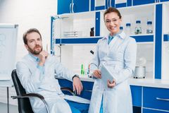 Portrait of scientific researchers in lab coats with digital tablet. In laboratory royalty free stock image