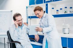 Portrait of scientific researchers in lab coats using digital tablet together. In laboratory stock photography