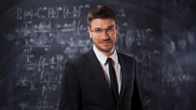 Portrait of scientist man standing near mathematical equations, formula. Portrait of scientist man with mathematical equations background. He put on his glasses stock video
