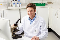 Portrait Of Scientist With Microscope In Laboratory Stock Image