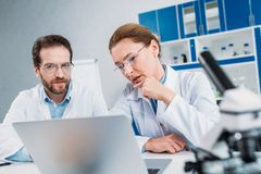 Portrait of scientists in lab coats and eyeglasses working together at workplace with laptop. In lab stock image