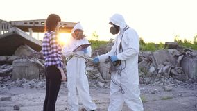 Portrait scientists in protective suits and masks and dosimeter ,measure radiation and affected people