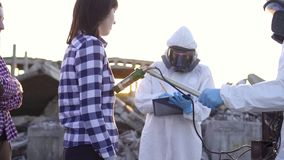Portrait scientists in protective suits and masks and personal ionizing radiation dosimeter ,measure radiation and