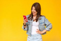 Portrait of screaming beautiful brunette young woman with makeup in denim casual style standing, shocked and looking at her red. Smart phone mobile. indoor royalty free stock image