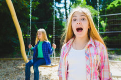 Portrait of screaming child at park. On the background other girl riding a swing Royalty Free Stock Photos