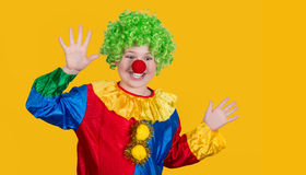 Portrait of a screaming clown with copyspace on yellow backgroun. D. Funny kid in green wig in clown costume Stock Photography