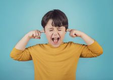 Portrait of a Screaming little boy covering ears with hands Stock Photo