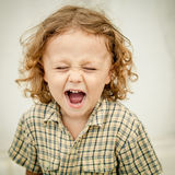 Portrait of a screaming little boy. At the day time Royalty Free Stock Image