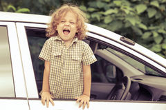 Portrait of a screaming little boy. Who sitting in the car Stock Images