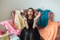 Portrait of a screaming pretty woman in dress sitting Stock Images