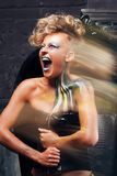 Portrait of screaming punk woman long exposure. Rocker girl with bright body art, make up and hairstyle, get away her pain. Distress, body art, aggression Royalty Free Stock Image