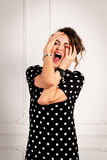 Portrait of a screaming sexy woman in a black dress Stock Image