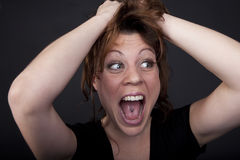 Portrait of a screaming woman. Screaming woman with hand in her red hairs Stock Photos