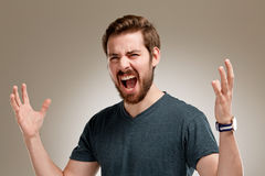 Portrait of screaming young man. With beard, on neutral background Stock Images
