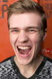 Portrait of screaming young man. In a gray sweatshirt on red rail container Stock Photography